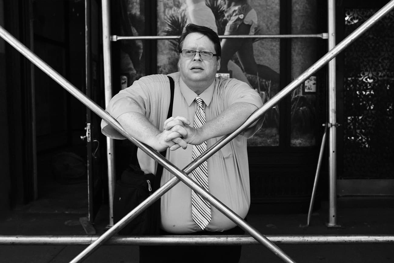 man learning against scaffolding X cross beams, looking tired after a day of work