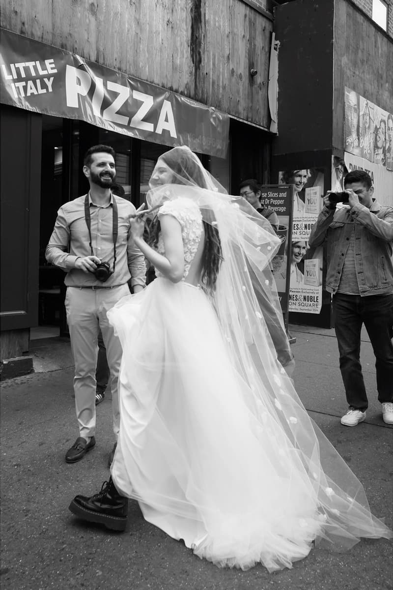 bride at street corner, wearing boots and being photographed by another person