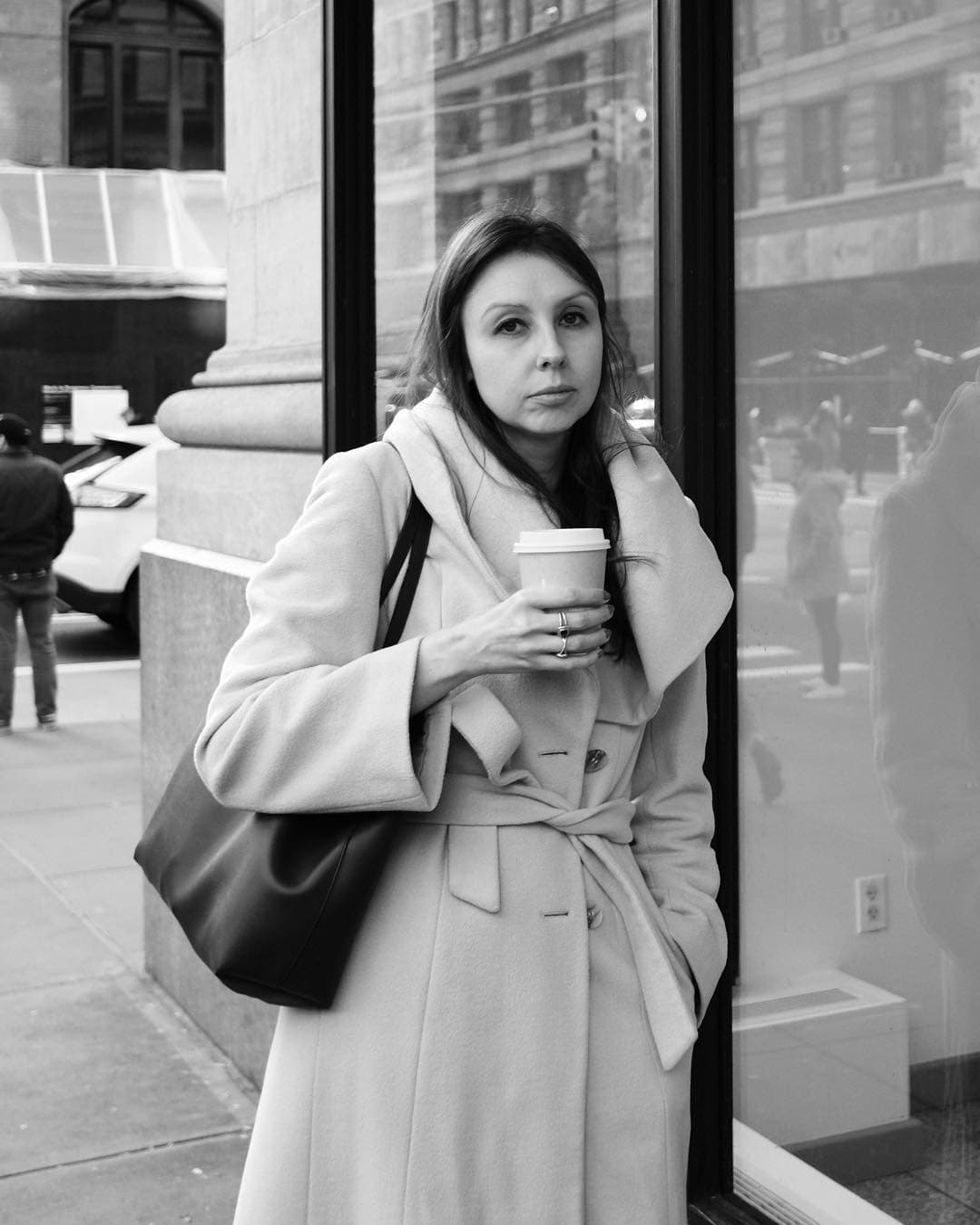 woman holding a coffee across from the flatiron building, standing against shop window and looking at the camera
