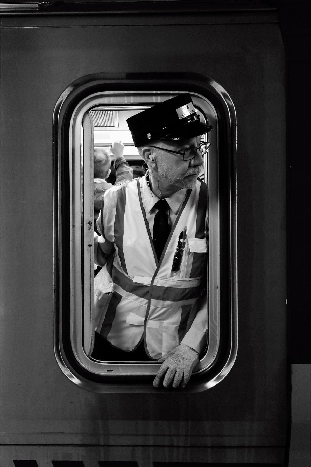 path train conductor at 14th street station staring ahead out of train window