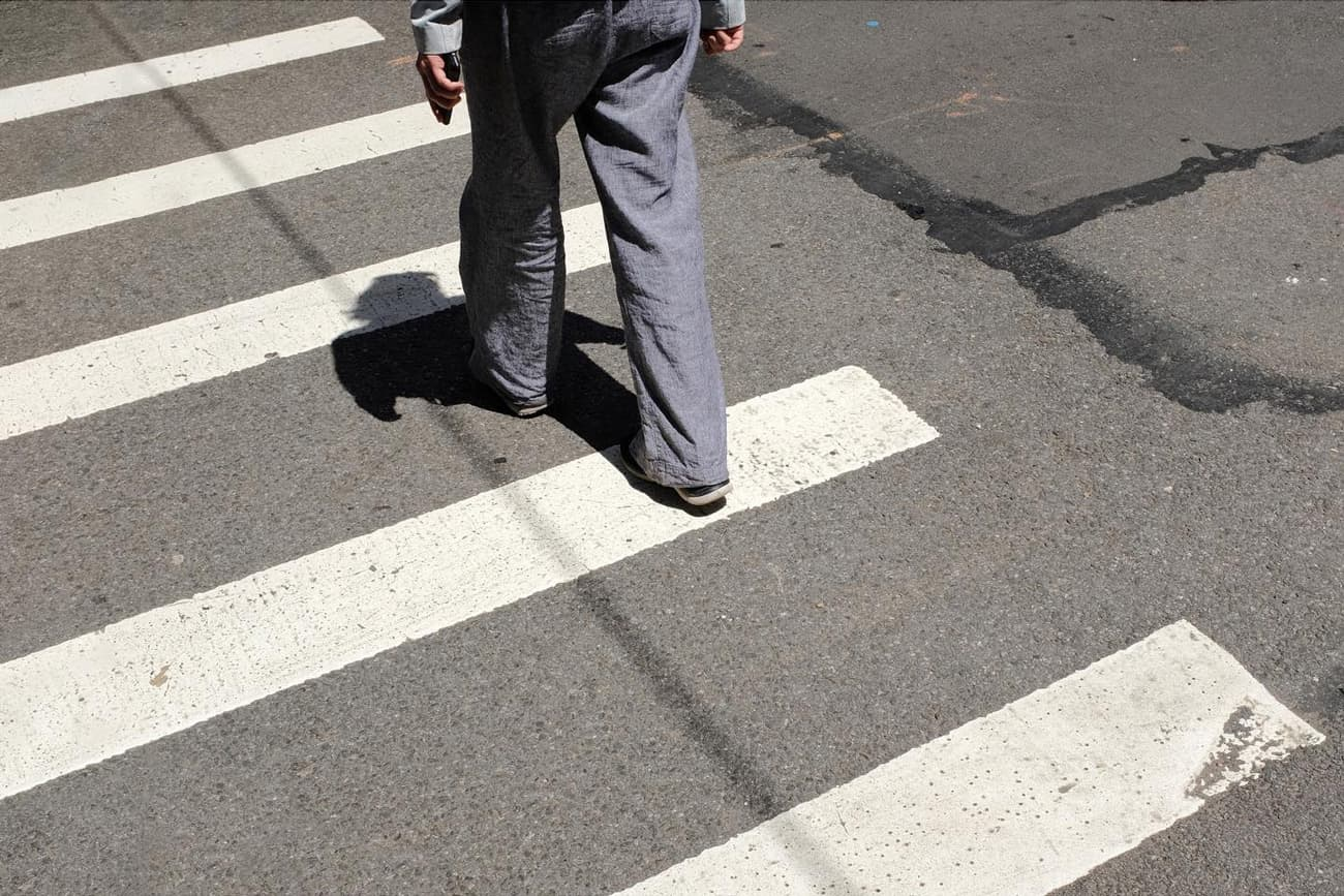 feet of man crossing the street, sidewalk paint lines show prominently