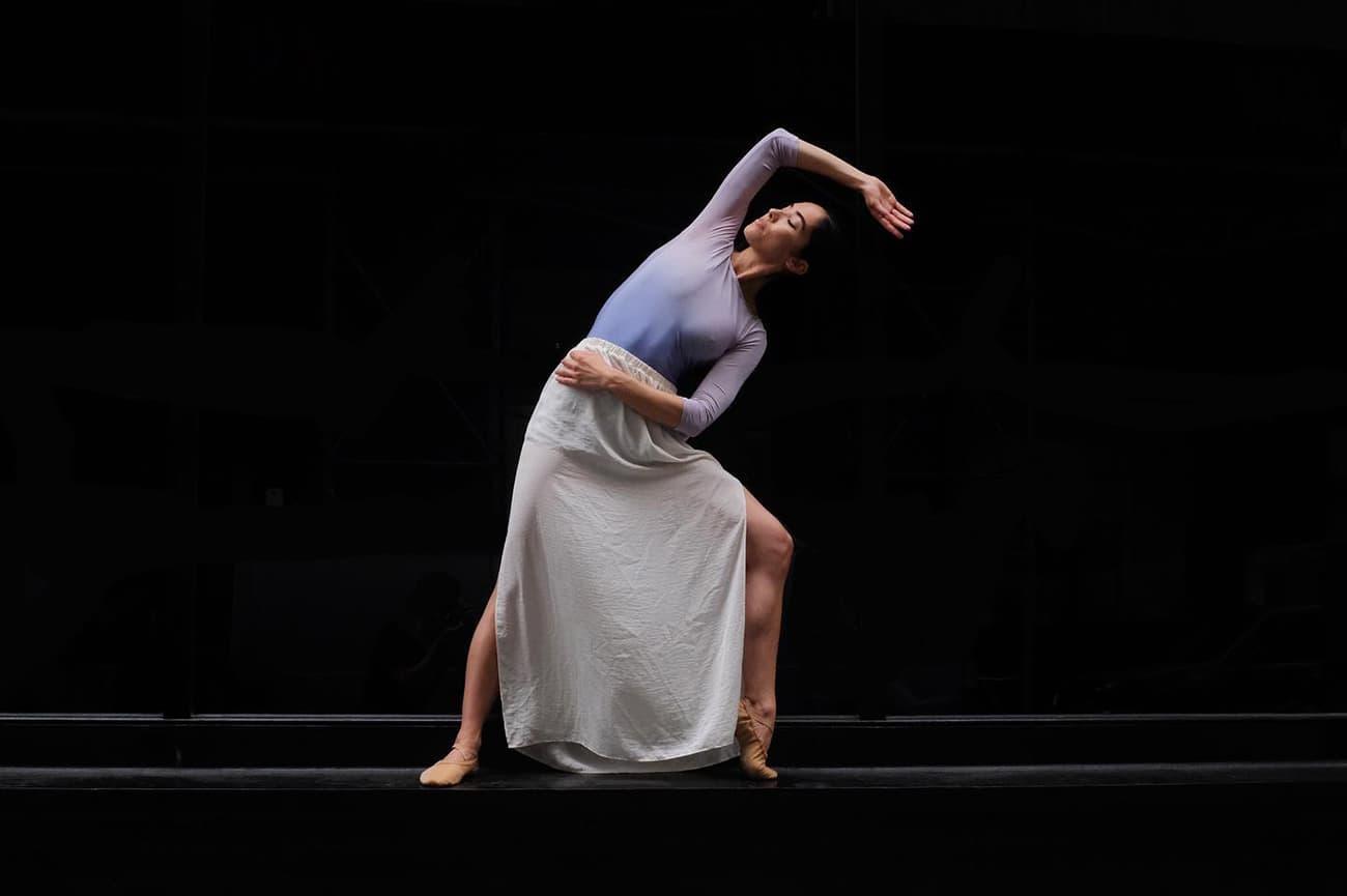 ballet dancer on a ledge against a black background