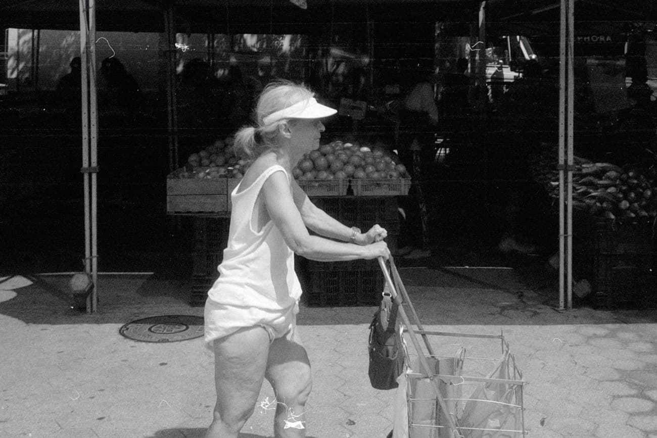 old woman pushing grocery cart in union square market, wearing nothing but a visor, t-shirt, and diaper