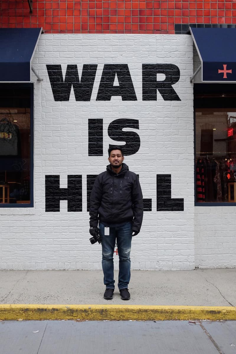 fahad standing in front of a restaurant wall with WAR IS HELL painted very large