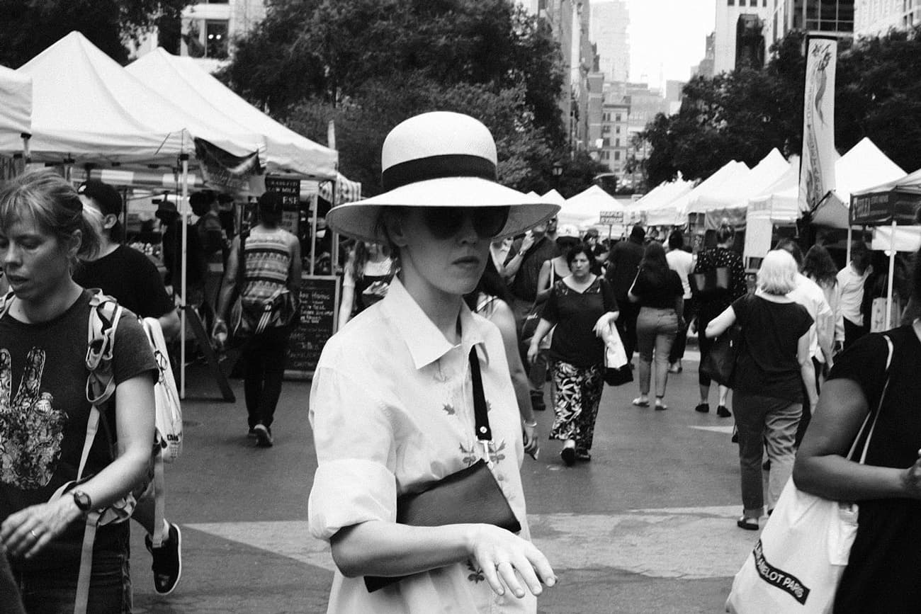woman wearing white hat at union square market that looks like vendor tents in the background