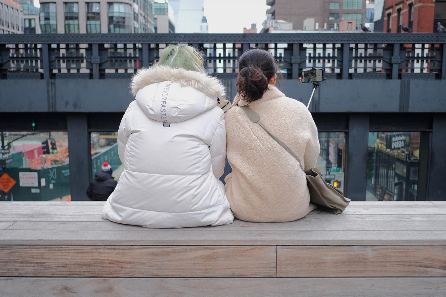 two girls sitting on step at the high line taking a selfie with phone mounted on stick