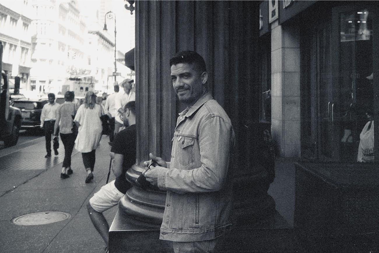 joey holding camera next to giant pillar, staring skeptically into camera