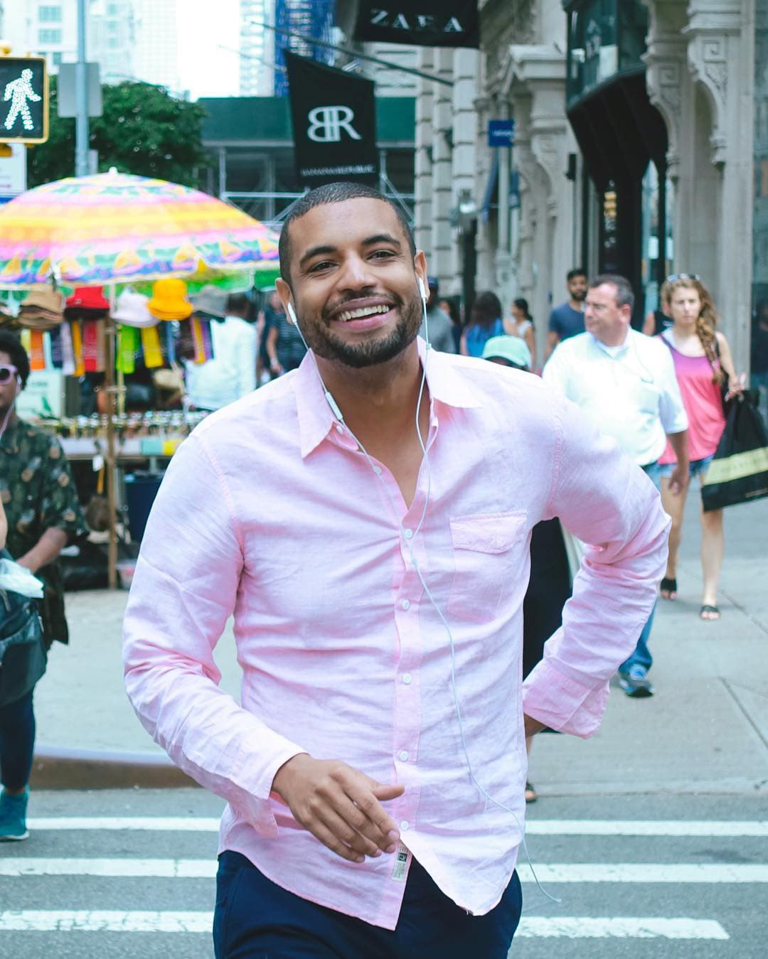 man crossing nyc street with swagger and smile on his face