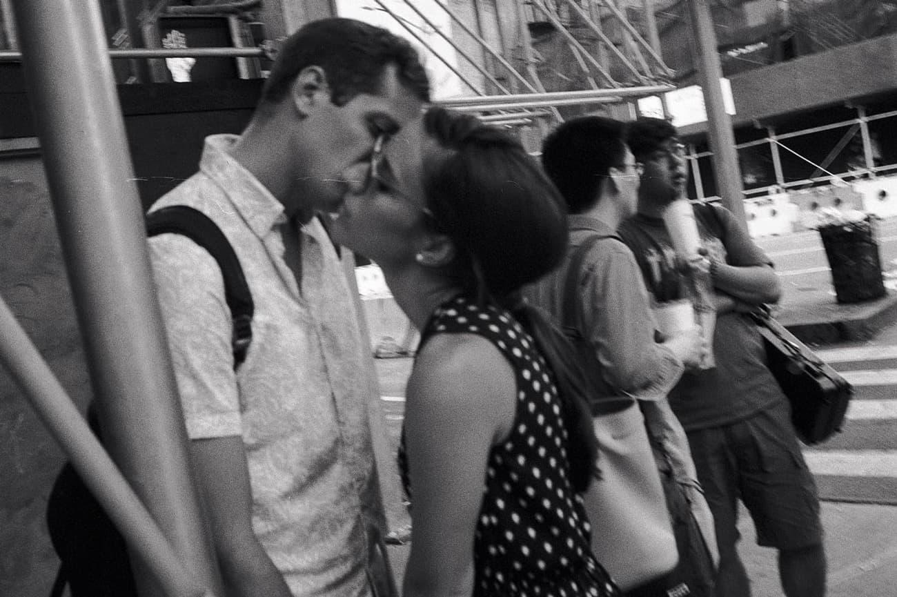 couple kissing atop subway entrance steps