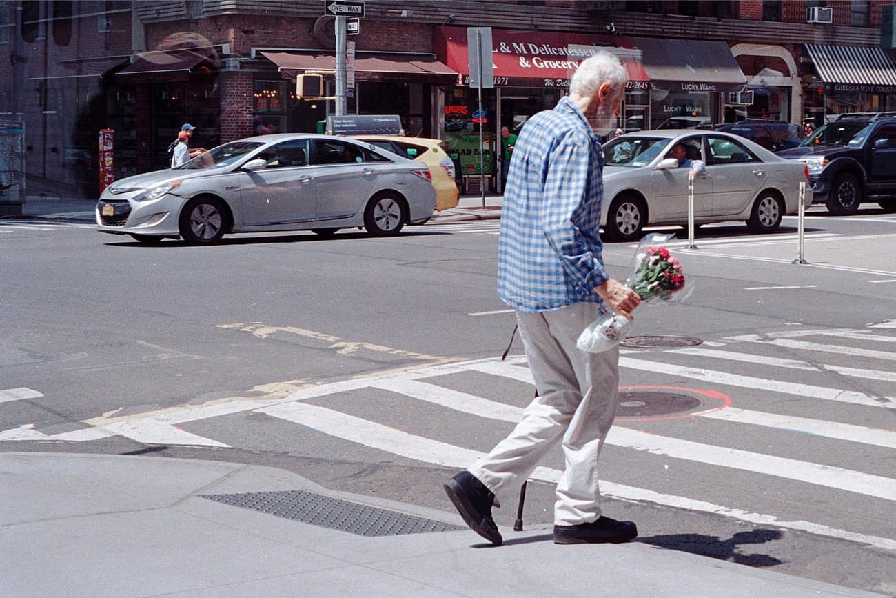 old man with cane crossing manhattan street with bouquet of flowers in hand