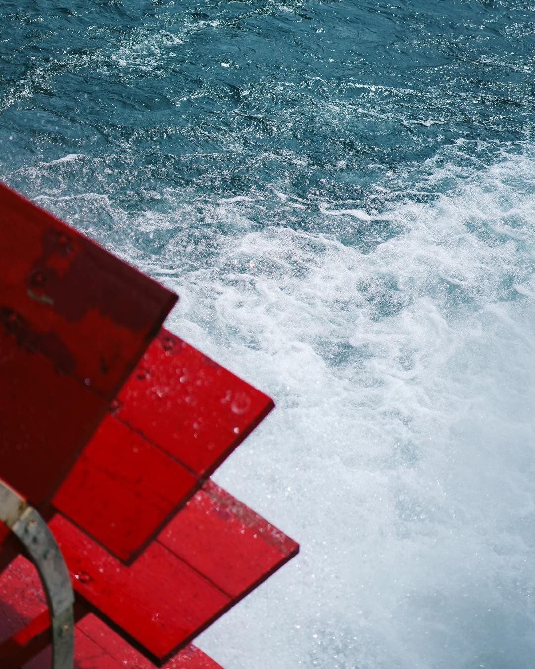 red wooden paddles on a boat with lots of water foaming in its trail