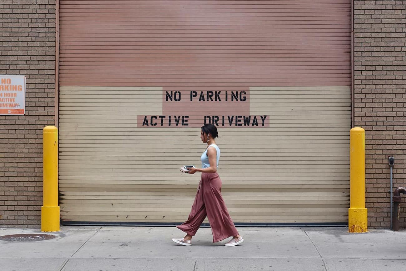 person walking in front of a garage door with NO PARKING ACTive DRIVEWAY message painted on it