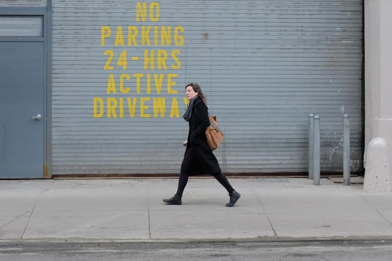 person walking in front of a garage door with NO PARKING 24-HRS ACTIVE DRIVEWAY painted in yellow on it