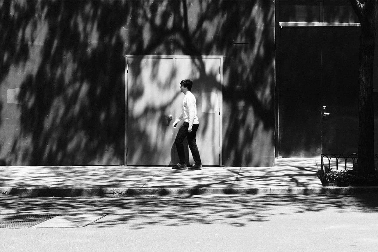 person walking in front of a door with leaf shadows all over the frame