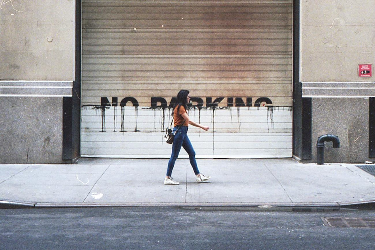 person walking in front of a garage door with 'no parking' painted on it