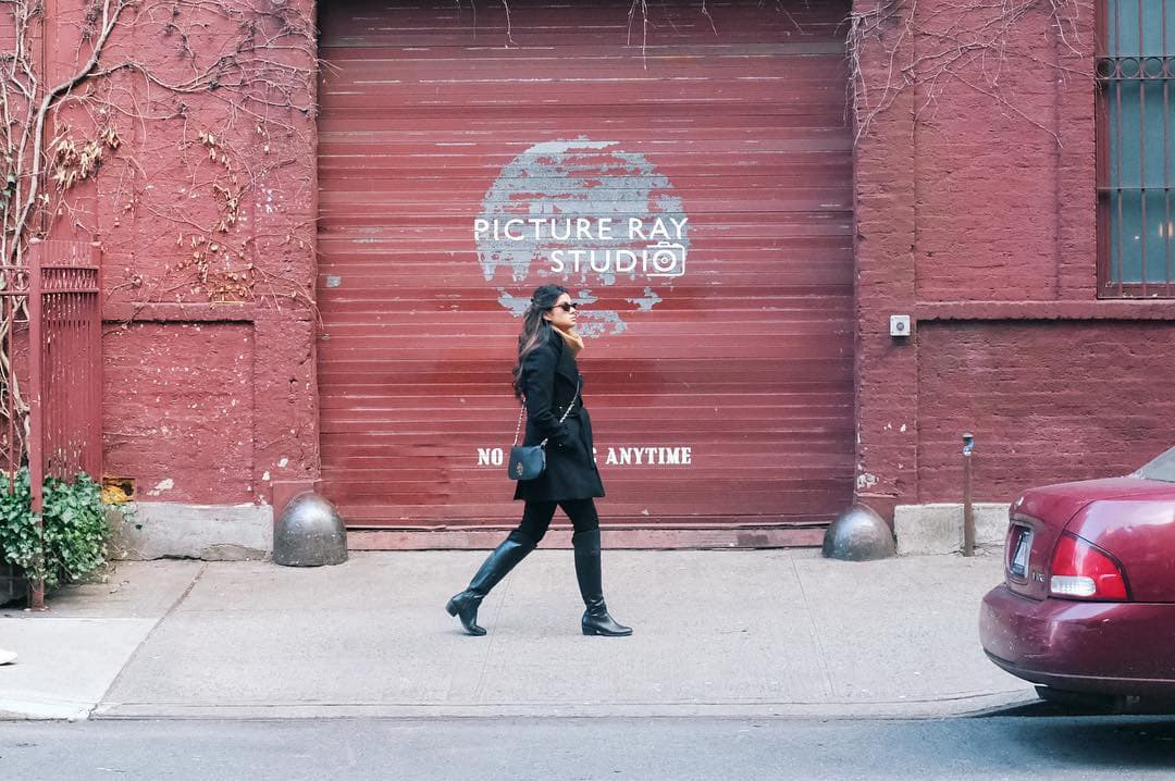 person walking in front of a red garage door with Picture Ray Studios written on it