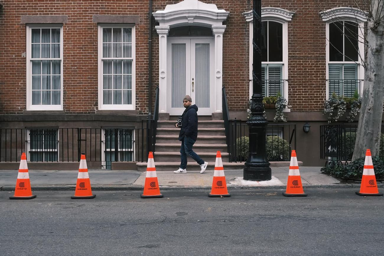 person walking in front of a building door, with parking cones neatly arranged on the street in front