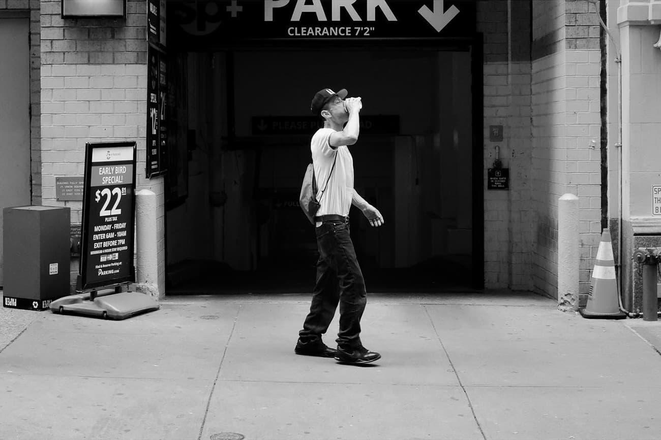 person walking in front of a parking garage door drinking a beer