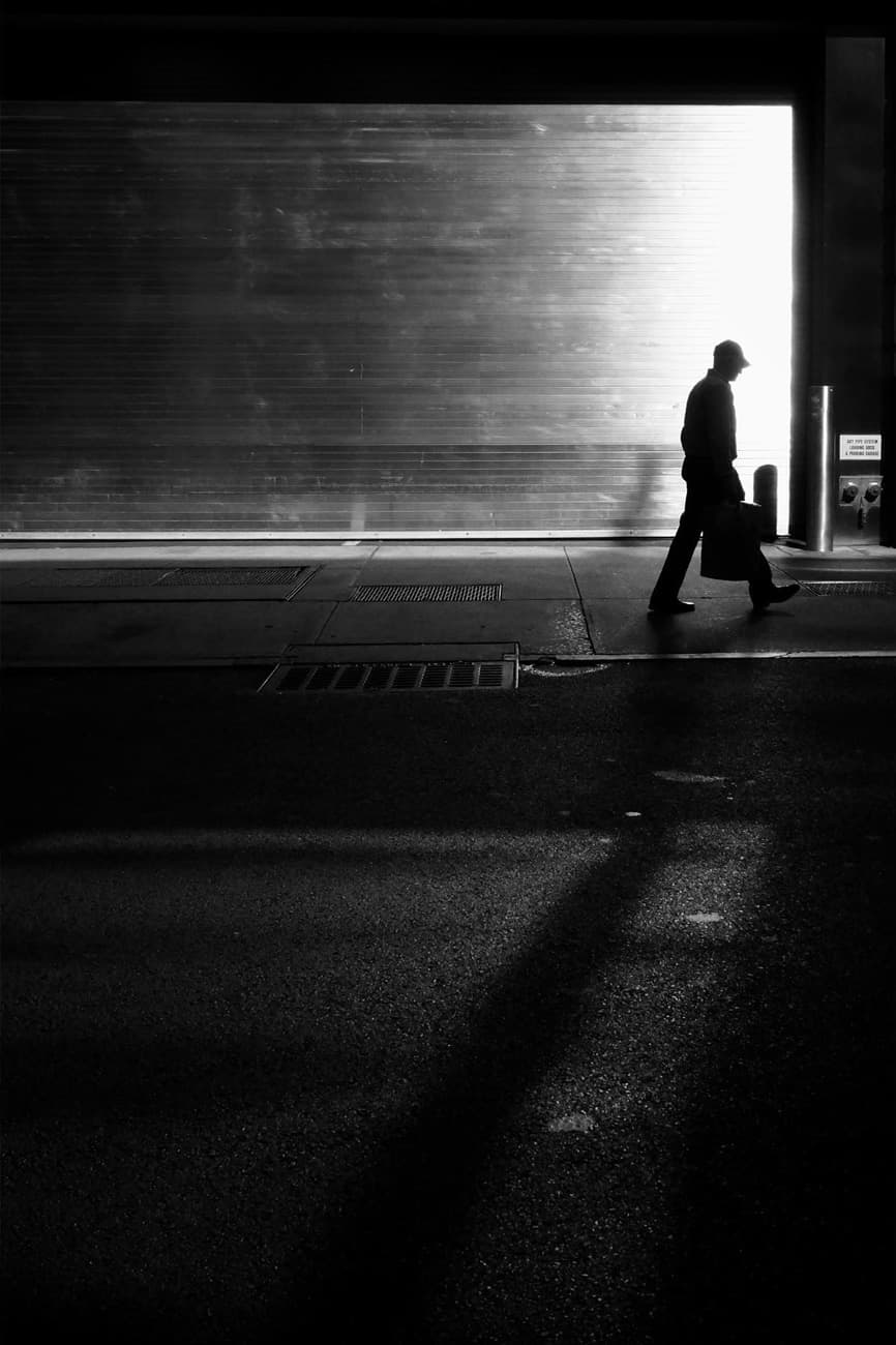 person walking in front of a garage door corner, a high contrast black and white photograph
