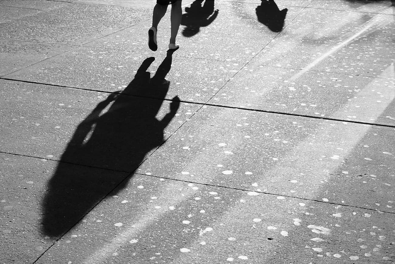 shadow of a person and lots of gum reflected in the sunshine of a new york city sidewalk