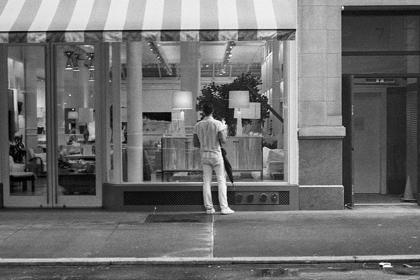 person staring into store window, wearing a striped shirt that matched the striped awning above him