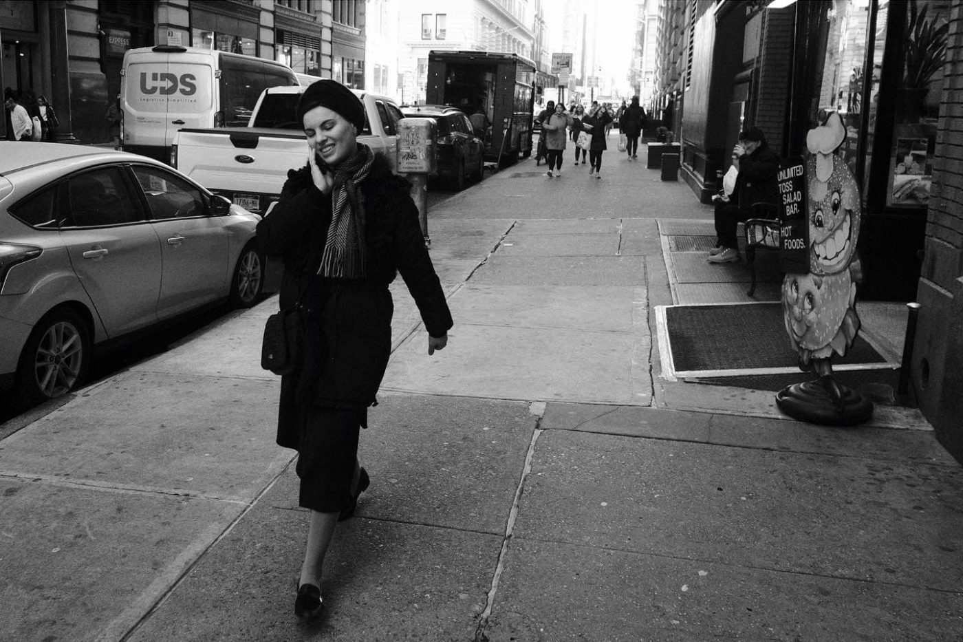 orthodox jewish woman walking while talking on phone, wearing smile on her face