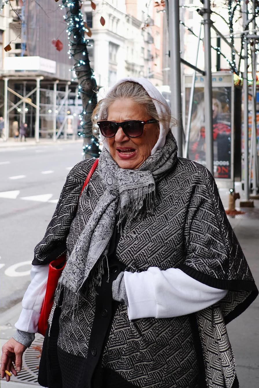 old lady wearing a scarf with cigarette in hand, wearing a shocked expression after the sound of a loud siren